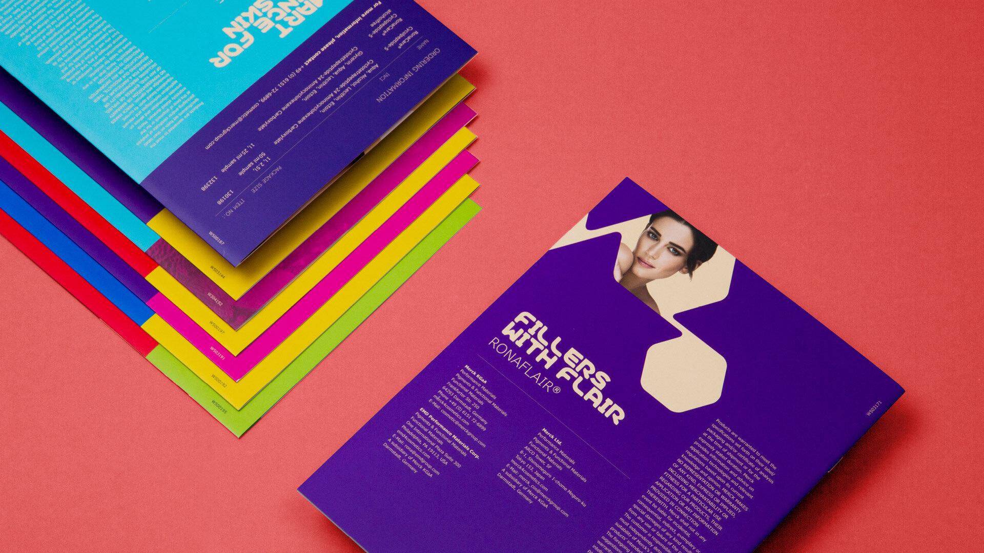 Rückseite einer violetten Broschüre und ein Stapel weiterer bunter Broschüren vor rotem Hintergrund