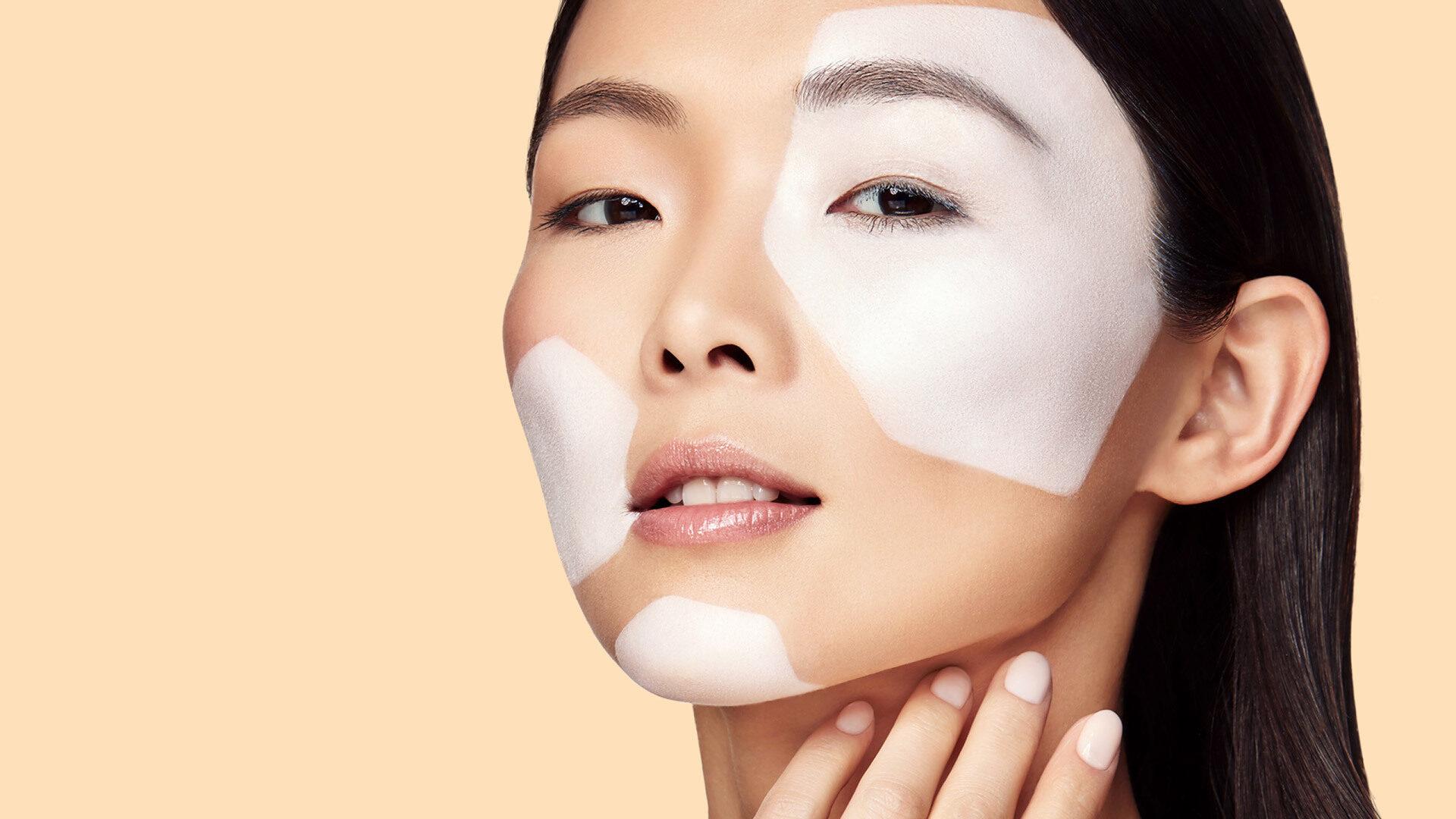 Portrait einer Frau mit weiß geschminkten Zellen im Gesicht vor beigem Hintergrund