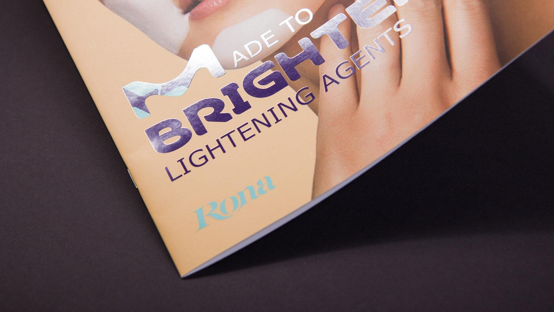 """Detail eines Broschürentitels mit violetter Headline """"Made to Brighten"""" und glänzendem Drucklack"""