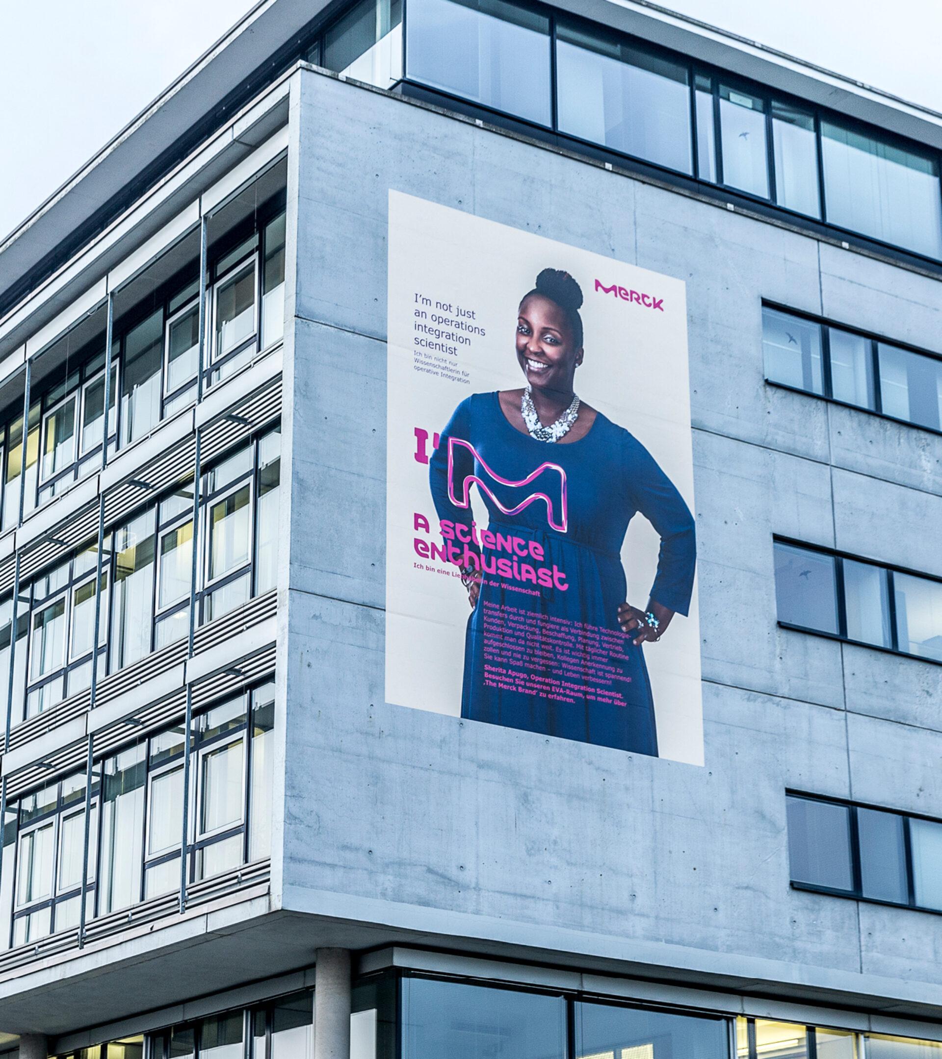 Zwei Stockwerke hohes beiges Plakat mit dem Portrait einer Merck Mitarbeiterin an einem Werksgebäude