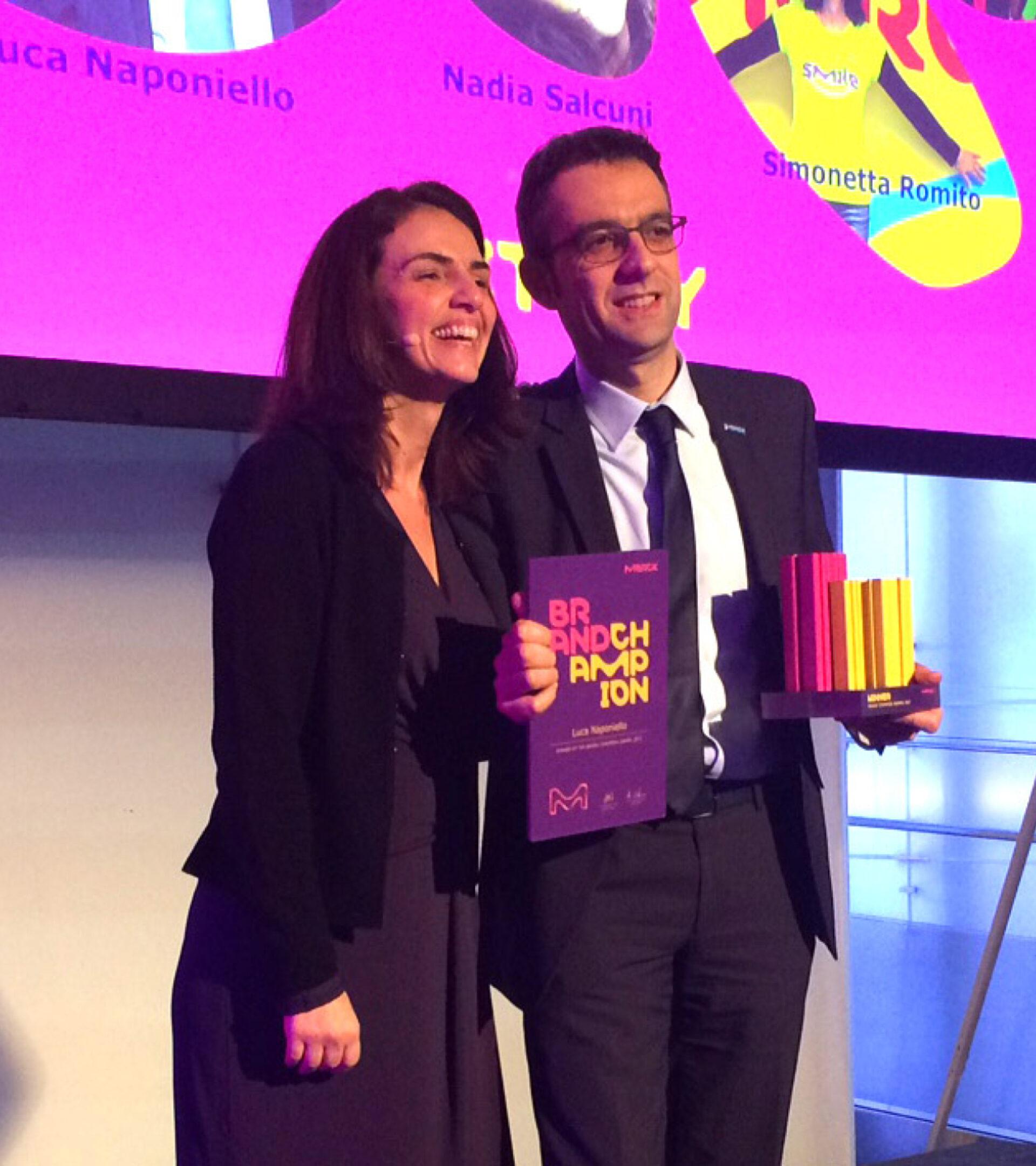 Zwei Personen halten den violett-gelben Brand Champion Award und die Auszeichnung