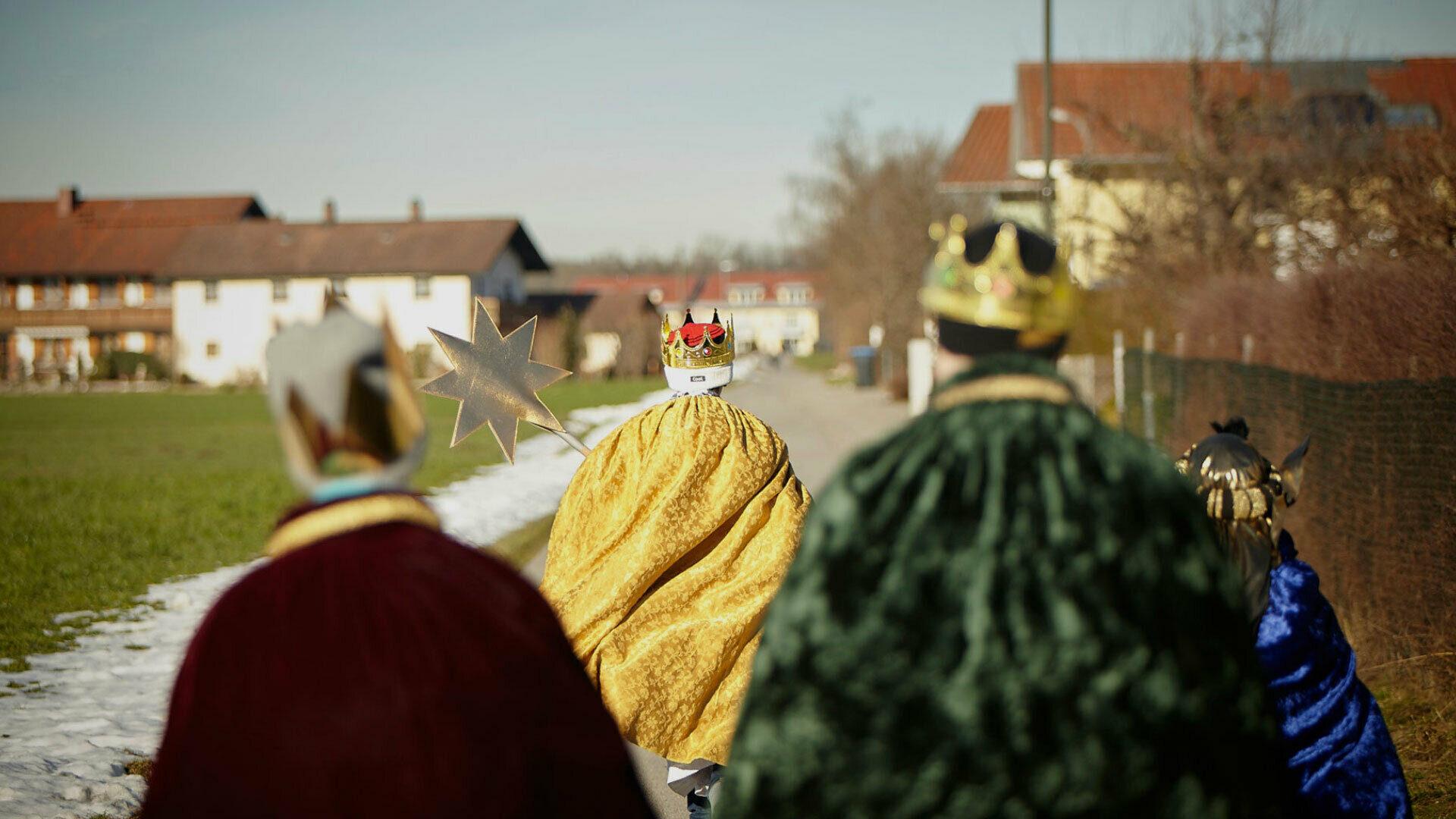 Sternsinger laufen durch ein Dorf