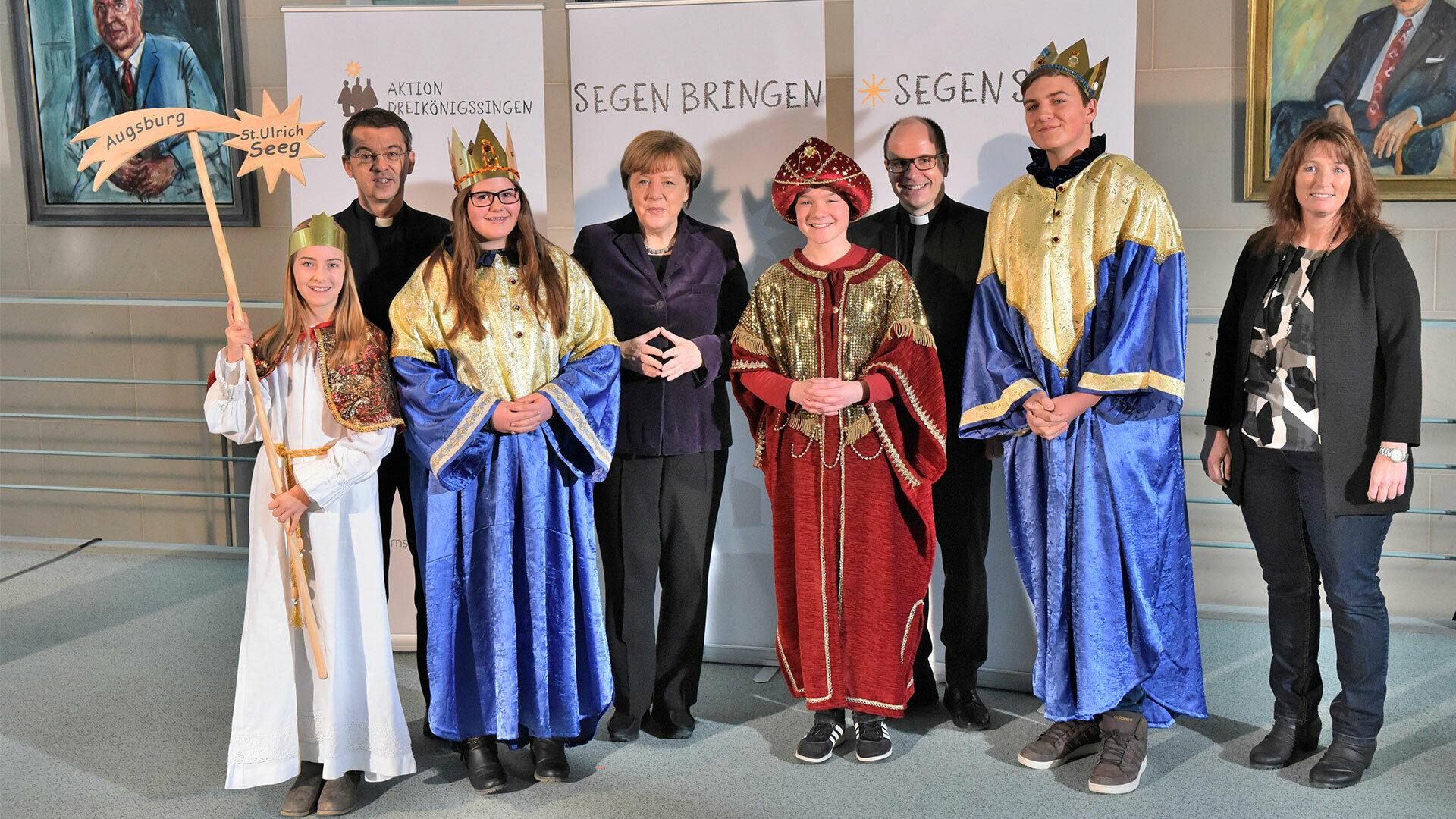 Vier kostümierte Sternsinger-Kinder sind zu Besuch bei Bundeskanzlerin Angela Merkel