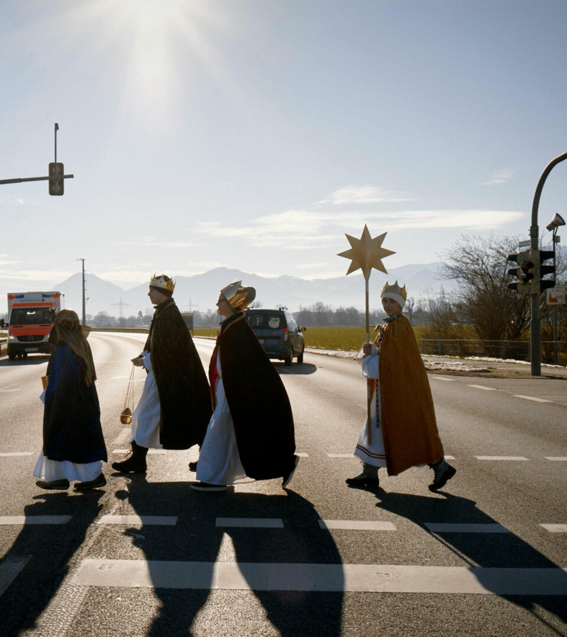 Vier Kinder in Sternsinger-Kleidung überqueren eine Straßenkreuzung